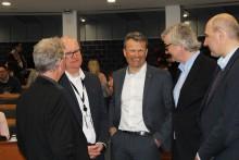 Fem menn i dress snakker sammen