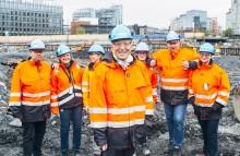 Mann i byggeklær omkranset av kolleger