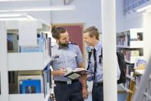 To menn i uniform snakker sammen i et bibliotek
